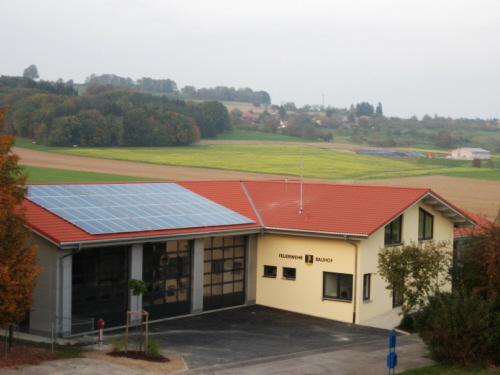 Zu sehen ist das Gerätehaus von einer erhöhten Position aus. Auf der rechten Seite ist die Fahrzeughalle zu sehen mit 3 Toren, auf dem Dach dieses Teils befindet sich eine Solaranlage. Im rechten Winkel dazu sind die übrigen Räumlichkeiten untergebracht,