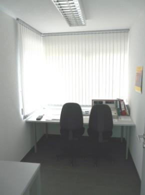 Zu sehen ist ein kleines Büro. Hier im Funkraum befinden sich zwei Stühle und ein Funkgerät.