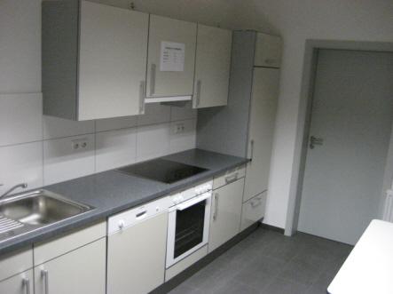 Die Küche ist mit Spülbecken, Spülmaschine, Backofen, Herd, Kühlschrank und mehreren Schränken ausgestattet.
