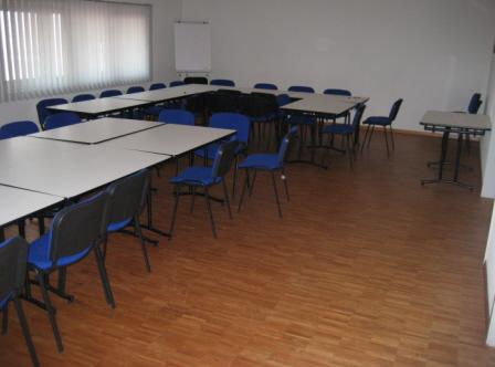 Der Schulungsraum ist mit ausreichend Tischen uns Stühlen ausgestattet. Hier im Bild sind diese im vorderen Bereich in U-Form angeordnet, im hinteren Bereich sind mehrere Tische zu einem Gruppentisch zusammengestellt.