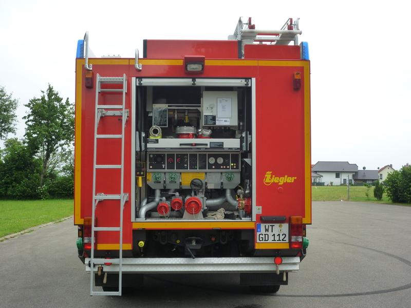 Heckansicht des Löschgruppenfahrzeugs LF 10/6: eine herausklappbare Leiter, sodass man auf das Dach gelangen kann. Außerdem ist die Pumpe und verschiedenes Kleinmaterial